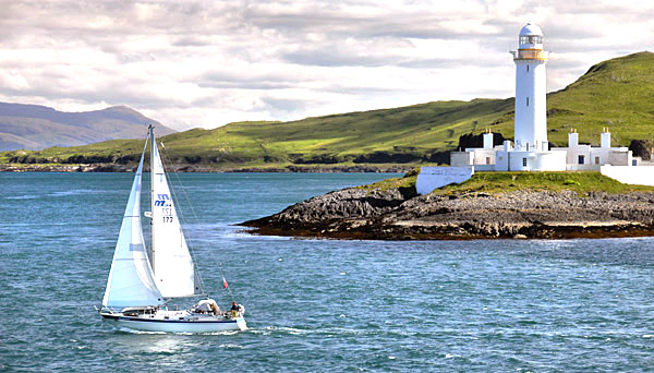 Eilean Musdile lighthouse and yacht, Scotland, UK